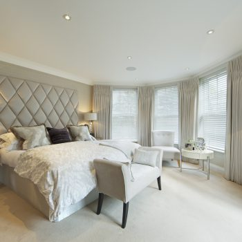 neutral coloured modern bedroom with venetian blinds and curtains on windows