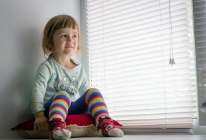 child sat next to venetian blinds