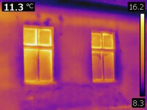 thermal image of the front of a house with heat escaping from windows