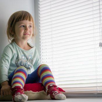 child sat next to venetian blinds